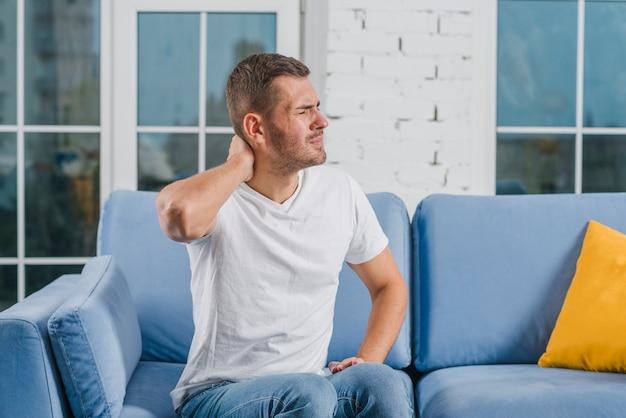 痛い首に苦しんでいる居心地の良いソファに座っているハンサムな男
