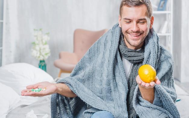 ピルの代わりにレモンを選ぶショールで包んだ笑顔の男