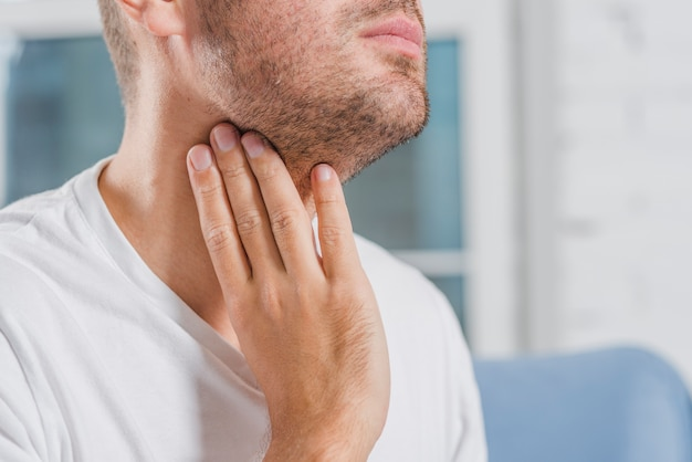 Крупный план мужской руки касаясь его горла