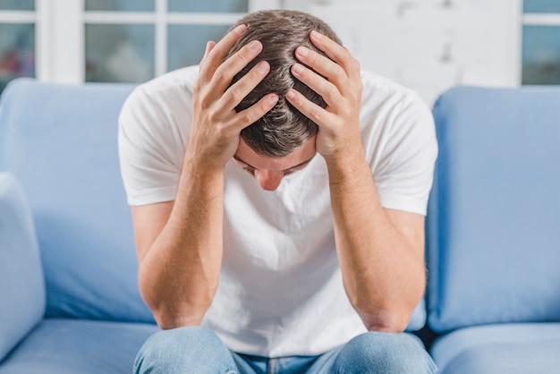 Разочарованный человек страдает от головной боли, сидя на диване