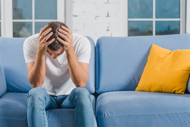 Взволнованный молодой человек, сидящий на синем диване, страдающий от головной боли