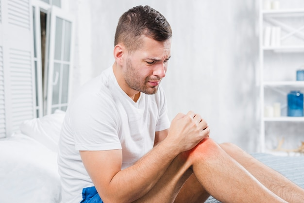 激しい痛みを伴う両手で膝を触れる男