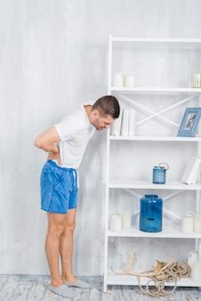 背中の痛みに苦しんでいる白い棚の近くに立っている若い男