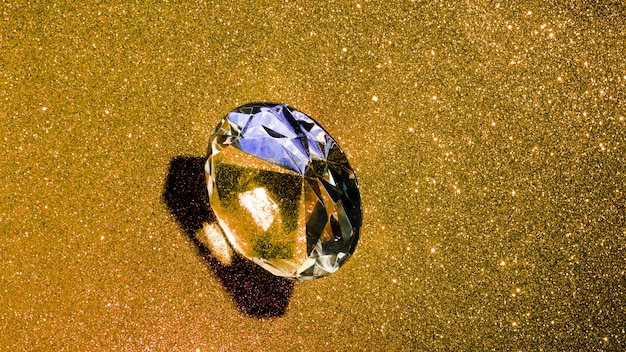光沢のある金色の背景に透明な光沢のあるダイヤモンド