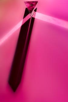 ピンクの背景に影を持つ長い水晶プリズムのクローズアップ