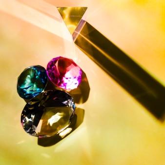 光沢のあるピンクのオーバーヘッドビュー。緑色と黄色のダイヤモンドは、色の背景に