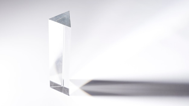 Прозрачная хрустальная призма с темной тенью на белом фоне