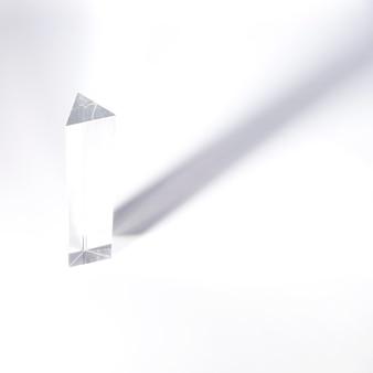 Длинный призматический кристалл с темной тенью на белом фоне
