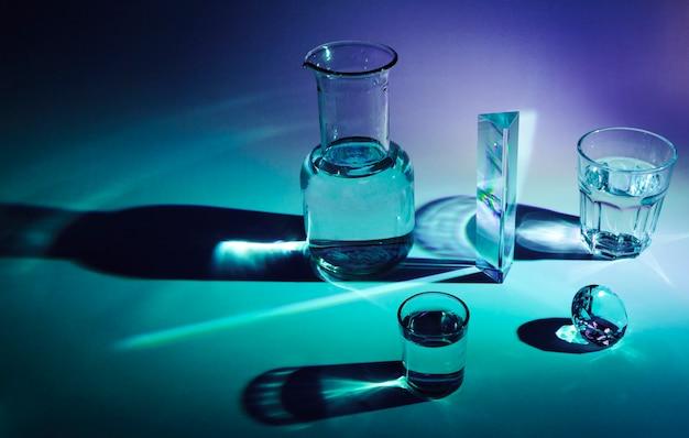 Блестящая бутылка; призмы; стакан; бриллиант с темной тенью на синем фоне