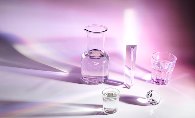 ビーカー;プリズム;色付きの背景に暗い影を持つガラスとクリスタルダイヤモンド