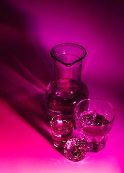 Вид сверху на прозрачные очки; мензурка и бриллиант на темно-розовом фоне