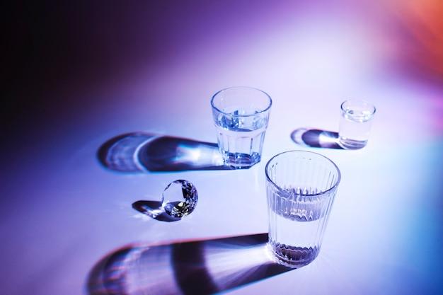 シャドウとカラフルな背景に飲み物のグラスとダイヤモンド