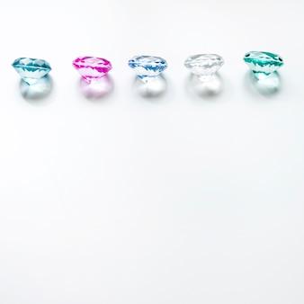 Ряд разноцветных бриллиантов с тенью на белом фоне