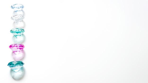 白い背景の上の影と光沢のあるカラフルなダイヤモンドのパノラマビュー