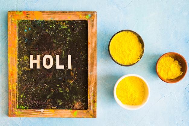 Холи текст на грязном деревянном сланце с желтой холи цветные чаши на окрашенном фоне