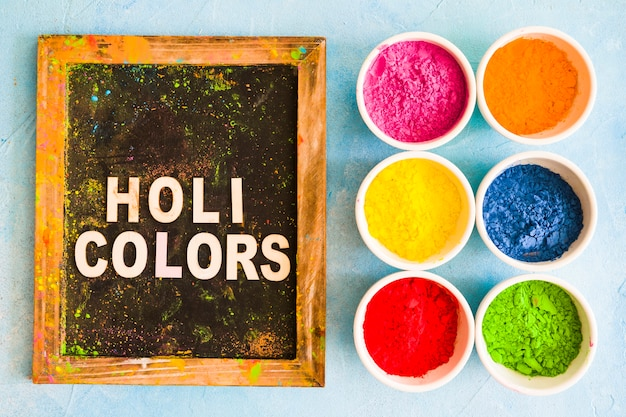 Цветная пудра в белых чашах возле деревянного сланца с цветным текстом холи