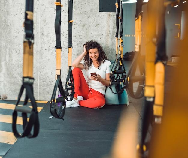 Ряд фитнес-ремень перед женщиной, слушать музыку на смартфоне