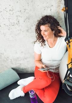 運動後に休憩をとり、ジムで携帯電話で音楽を聴く女性