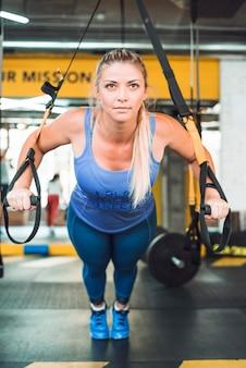 ジムでフィットネストラップで運動をしている美しい女性
