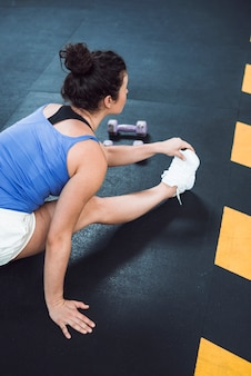 Подходит женщина, вытянув ногу в фитнес-клубе