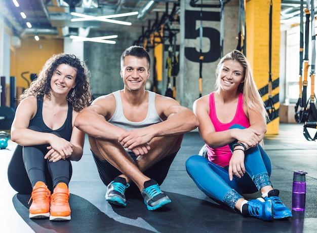 ジムで床に座っている幸せな運動の人々のグループ