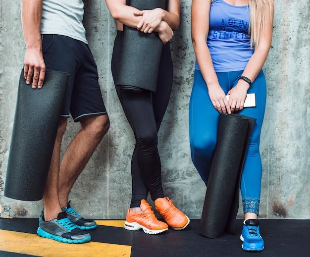 Низкий вид людей с тренировочным матом в спортзале