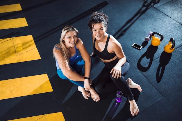 Портрет двух улыбающихся молодая женщина, сидящая в фитнес-клубе