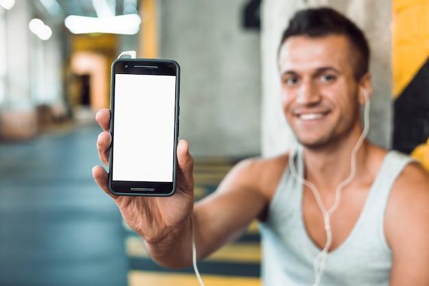 空白の白い画面を持つ携帯電話を持って笑顔の若い女性