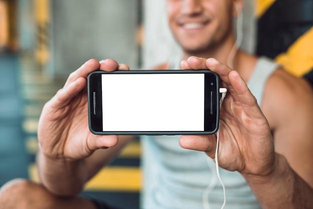 空白の白い画面を持つ携帯電話を示す人間の手のクローズアップ