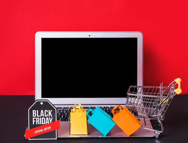Ноутбук возле игрушечных мешков, знак и корзина для супермаркетов