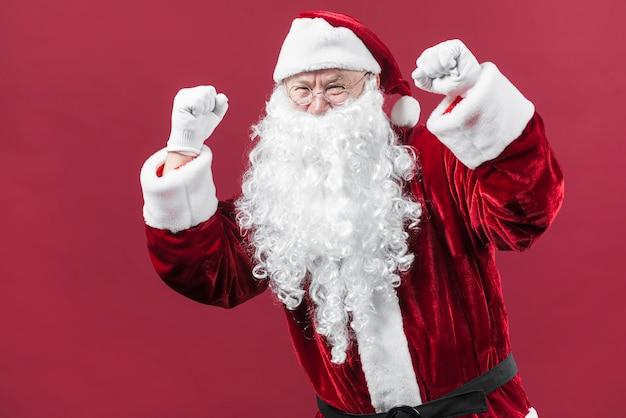 サンタクロース、帽子、拳を見せる