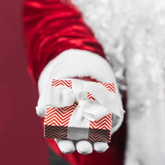 Санта-клаус держит подарочную коробку в руке