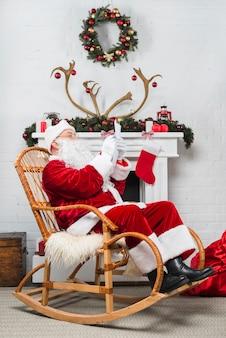 Санта, сидящий в качалке с записью