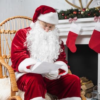 Санта сидит в качалке и делает заметки