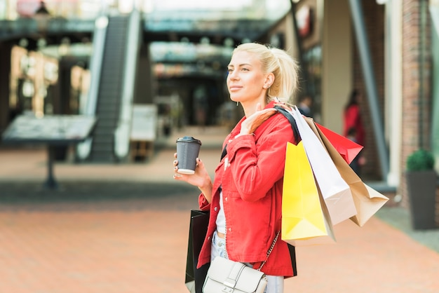 買い物用のパケットとドリンクのカップを持つ女性
