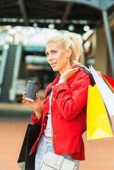買い物のパケットとドリンクのカップを持つ女性