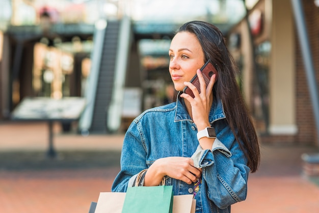 モールのショッピングバッグとスマートフォンを持つ女性