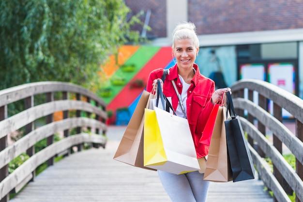 買い物のパケットを持つ笑顔の女性