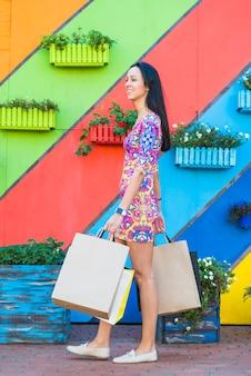 Женщина с пакетами возле стены