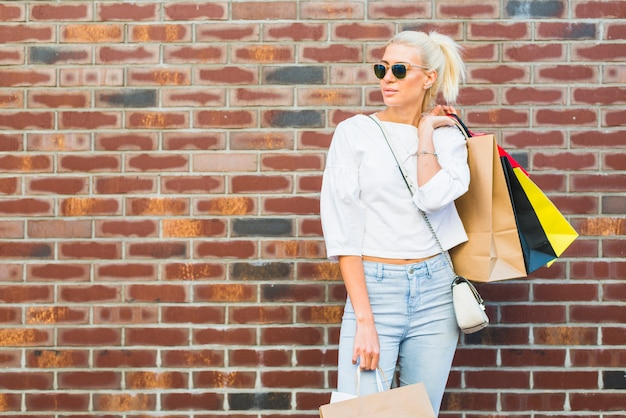 Красивая женщина с пакетами возле стены