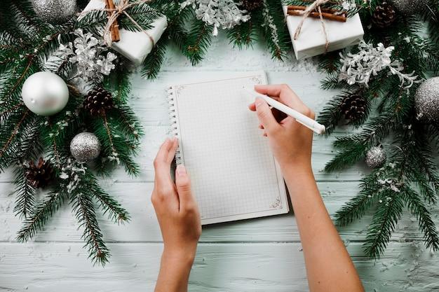 クリスマスの枝の近くの手帳で手