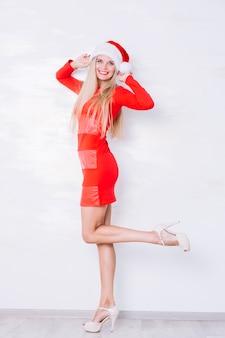 白い壁の背景に立っている赤いドレスの女性