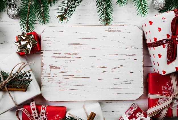 ギフトボックスを備えた木製ボードのクリスマスの組成