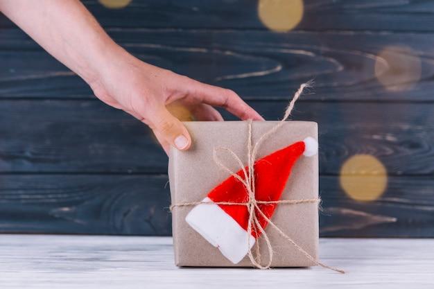 Женщина, держащая подарочную коробку с маленькой шляпой санта