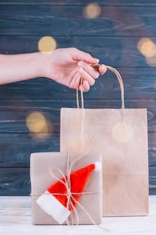 Женщина, держащая подарочный мешок рядом с подарочной коробкой