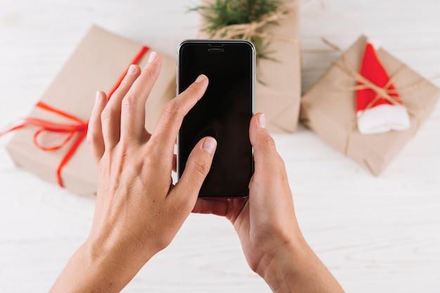 Женщина, держащая смартфон перед подарочными коробками