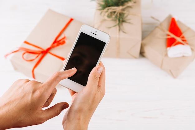 Женщина, держащая смартфон над маленькими подарочными коробками