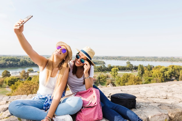 Две счастливые женщины-друзья, берущие себя на мобильный телефон
