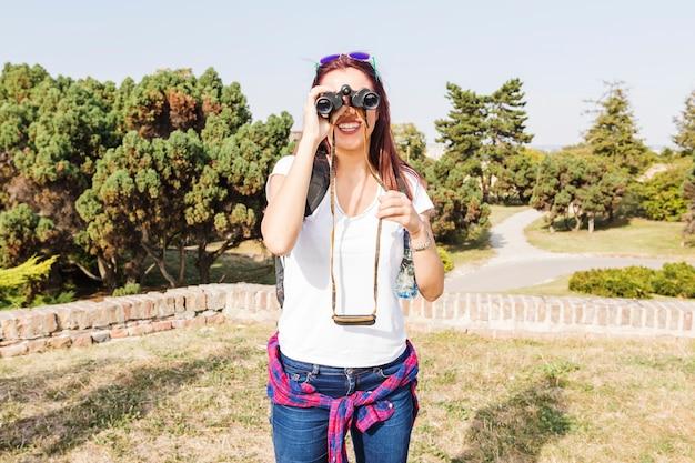 双眼鏡を見ている幸せな女性の登山人