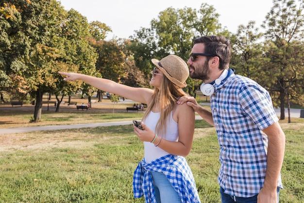 屋外で彼女のボーイフレンドに何かを示す若い女性